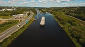 waterway : Aerial view:Barge with cargo on the river. River, cargo barge, highway with cars.. Cargo ship on the river.4K, aerial footage. Stock Footage