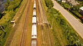 vagón : Freight train with cisterns and containers on the railway. Aerial view Container Freight Train, Locomotive in the countryside, Railway and highway. 4K, flying video, aerial footage.