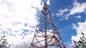 telewizor : Cell phone tower against a blue sky. Tower of communications with a lot of different antennas under blue sky and clouds. Telecommunication tower with blue sky. 4K video