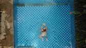 aktivity ve volném čase : Young girl in a swimming suit in blue water pool. Aerial view girl swims in the pool of the resort, 4k.