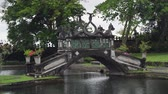 bahçe : Hindu Balinese Water Palace Tirta Gangga with old bridge on Bali island, Indonesia. Tirta Gangga the former royal water palace is a maze of pools and fountains surrounded by a lush garden and stone carvings and statues. Stok Video