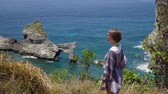пики : Young girl stands on the edge of a cliff and looks at the sea. Girl on the edge of the cliff enjoys the view of the ocean. Atuh beach on Nusa Penida island. 4K video. Travel concept.
