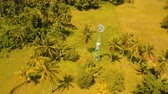 лезвия : Small wind turbine to produce electricity among palm trees and a farm field. Aerial view:Small wind turbine in motion.Small windmills. Philippines, Siargao. 4K video. Aerial footage. Стоковые видеозаписи