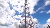 sinais : Cell phone tower against a blue sky. Tower of communications with a lot of different antennas under blue sky and clouds. Telecommunication tower with blue sky. 4K video