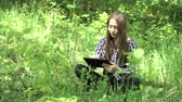 dospívající dívky : Teenage girl using tablet in green park. Cute young girl with digital tablet in a summer forest. 4K video