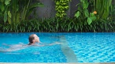 yüzme : Young girl in a swimming suit in blue water pool. Girl swims in the pool of the resort, 4k.Travel concept