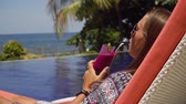 kaluž : Beautiful young girl with glass of cocktail relaxing near swimming pool. Girl in sunglasses with cocktail in seafront near the bassin amongst the palm trees on the background of the sea. Travel, vacation concept. Dostupné videozáznamy