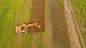 escavador : Excavator is digging an irrigation canal. Aerial view:Excavator digging a deep trench.excavator is digging an drainage canal in the agricultural field.4K Vídeos
