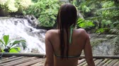 quedas : Girl sits on a wooden flooring in rainforest and looks at beautiful waterfall. Bikini girl sitting next to idyllic tropical waterfall. Bali,Indonesia.
