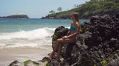пики : Beautiful girl in bikini sitting on a rock above the sea and looking at ocean. Girl on the tropical beach, Bali, Indonesia. Travel concept, 4K video. 4K video. Travel concept. Стоковые видеозаписи