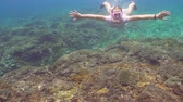 búvár : Young girl in a mask and a tube dives under the water. Girl snorkelling underwater. Tourist having fun diving in crystalline blue water, Happy tourist on vacation.
