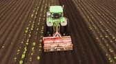 agronomia : Aerial view Tractor Hilling Potatoes with disc hiller. Farmer in tractor preparing land with seedbed cultivator in farmlands. Tractor plows a field. Agricultural work in processing, cultivation of land. Farmers preparing land and fertilizing. Agricultural Stock Footage