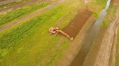 kbelík : Excavator is digging an irrigation canal. Aerial view:Excavator digging a deep trench.excavator is digging an drainage canal in the agricultural field.4K Dostupné videozáznamy
