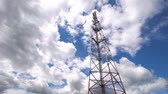 transmissor : Cell phone tower against a blue sky. Tower of communications with a lot of different antennas under blue sky and clouds. Telecommunication tower with blue sky. 4K video