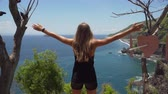 Бали : Young girl stands on the edge of a cliff and looks at the sea. Girl on the edge of the cliff enjoys the view of the ocean. 4K video. Travel concept. Стоковые видеозаписи