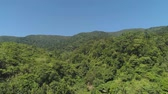 vadi : Aerial view of mountains with green forest, trees, jungle with blue sky. Slopes of mountains with tropical rainforest. Philippines, Luzon. Tropical landscape in Asia.