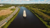 watercraft : Aerial view:Barge with cargo on the river. River, cargo barge, highway with cars.. Cargo ship on the river.4K, aerial footage. Stock Footage