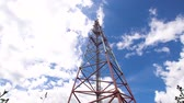 передатчик : Cell phone tower against a blue sky. Tower of communications with a lot of different antennas under blue sky and clouds. Telecommunication tower with blue sky. 4K video