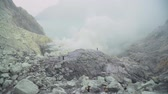 montão : Extraction of sulfur in the crater of a volcano. Sulfur, sulfur gas, smoke. Kawah Ijen, crater with acidic crater lake where sulfur is mined. Ijen volcano complex is a group of stratovolcanoes in the Banyuwangi Regency of East Java, Indonesia. Stock Footage
