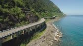 montão : Aerial view of Patapat viaduct in the coast of Pagudpud, Ilocos Norte. Highway with bridge by coast sea near the mountains. Philippines, Luzon.