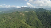 havadan görünüş : Aerial view of mountains covered with green forest, trees with blue sky. Slopes of mountains with tropical forest. Philippines, ,Luzon. Tropical landscape in Asia. Stok Video