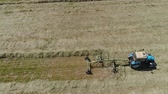 farming equipment : Aerial, view agricultural machinery with wheeled rake makes ranks beveled hay.Tractor which is lining up dried grass getting it ready for pickup so it can be used as animal fodder summer day. Stock Footage