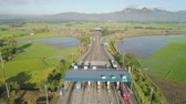 способ : Highway with a toll payment point. Aerial view: Cars passing through the point of toll highway, toll station,Philippines, Luzon. Drone view on toll collection point on the motorway. Стоковые видеозаписи
