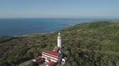 ilocos : Aerial view of Lighthouse on hill. Cape Bojeador Lighthouse, Burgos, Ilocos Norte, Philippines. Stock Footage