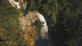 vodopád : aerial footage waterfall in the mountains. Waterfall flowing on the slopes of mountains covered with tropical vegetation. Philippines, Luzon