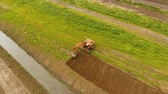 épít : Excavator is digging an irrigation canal. Aerial view:Excavator digging a deep trench.excavator is digging an drainage canal in the agricultural field.4K Stock mozgókép