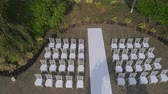 událost : aerial footage wedding ceremony with arch decorated with cloth and flowers outdoor. wedding set up in the park on a sunny day, arch and chairs for guests