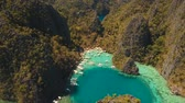 рай : Aerial tropical lagoon with azure water and coral reef among rocks with tropical vegetation Kayangan Lake, Palawan, Philippines Travel concept, Aerial footage. Стоковые видеозаписи