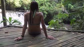Girl sits on a wooden flooring in rainforest and looks at beautiful waterfall. Bikini girl sitting next to idyllic tropical waterfall. Bali,Indonesia.