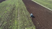 Aerial view of tractor plows the agricultural land for sowing. Plowing farming land.