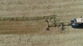 haymaking : Aerial, view agricultural machinery with wheeled rake makes ranks beveled hay.Tractor which is lining up dried grass getting it ready for pickup so it can be used as animal fodder summer day. Stock Footage