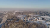 field ice : aerial view village among the fields and forests in winter. winter landscape snow covered field and trees in countryside. Stock Footage