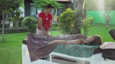 massage therapie : Asian woman massage therapist doing massage to girl. Summer vacation on luxury spa resort, massage procedure on the beach. Young woman enjoying a massage outside. Bali,Indonesia. Stockvideo