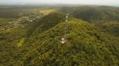 トランスミッタ : aerial footage telecommunication tower located located in mountainous province. cellphone tower in rainforest white telecom radio tower