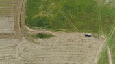 fazenda : Aerial, view agricultural machinery with wheeled rake makes ranks beveled hay.Tractor which is lining up dried grass getting it ready for pickup so it can be used as animal fodder summer day. Stock Footage