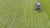 mowing : Tractor mowing grass with a disc mower for animal feed. Aerial view Preparation feed silage with mower mounted on tractor. Stock Footage