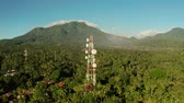 transmissor : Antennas and microwaves link dishes of mobile phone network and TV transmitter on telecommunication towers with mountains and rainforest. Camiguin, Philippines