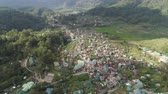 mezők : Aerial view town Sagada, located in mountainous province of Philippines. City in valley among mountains covered with forest. Stock mozgókép