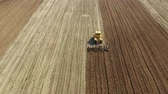 çiftçilik : aerial view farm tractor with disk plow preparing land for sowing. Tractor with harrows prepares the agricultural land for planting crop. Cultivation of farmland by disc harrows. Stok Video