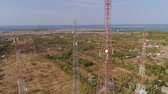 передатчик : aerial view cell phone towers line in bali, indonesia. Telecommunication tower, communication antenna on coast sea Стоковые видеозаписи