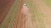 maquinaria : Tractor Hilling Potatoes with disc hiller in a potato field top view. Farmer in tractor preparing land with seedbed cultivator in farmlands