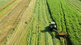 maquinaria : Aerial view of a tractor mowing a green fresh grass field, a farmer in a modern tractor mowing a green fresh grass field on a sunny day