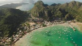 Aerial view of town of El Nido in the bay with the blue lagoon and tourist boats. Famous tourist place on the island of Palawan. Seascape with blue bay and boats view from above. Summer and travel vacation concept