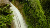 Aerial view of Inambakan waterfalls in a mountain gorge in the tropical jungle, Philippines, Cebu. Waterfall in the tropical forest.