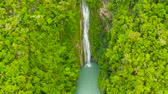 Waterfall in the rainforest jungle from above. Tropical Mantayupan Falls in mountain jungle. Philippines, Cebu.