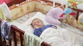 teething : newborn baby boy in blue clothes is awake in the crib